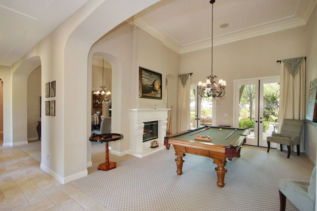 Traditional Game Room with simple marble floors, Chandelier, Columns, High ceiling, French doors, Fireplace, insert fireplace