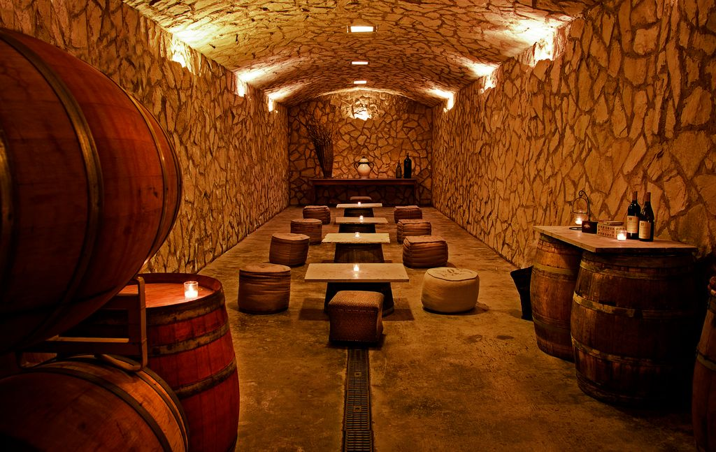 Rustic Wine Cellar with Deco home vintage sack ottoman, Standard height, can lights, Interior stone wall, Built-in bookshelf