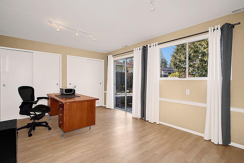 Traditional Home Office with Chair rail, Laminate floors, flush light, Standard height, sliding glass door, Casement