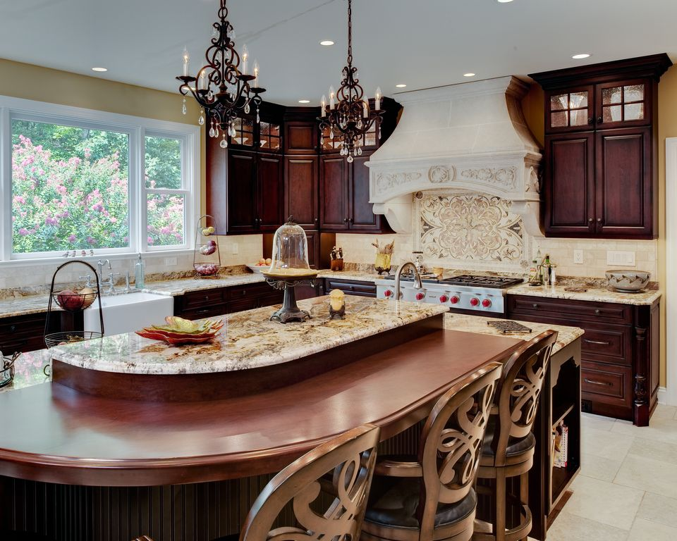 Traditional Kitchen with Limestone Tile, electric cooktop, stone tile floors, Kitchen island, can lights, Custom hood