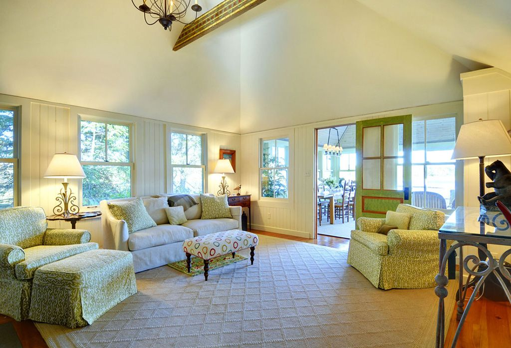 Cottage Living Room with High ceiling, Exposed beam, Glass panel door, double-hung window, Hardwood floors, Chandelier