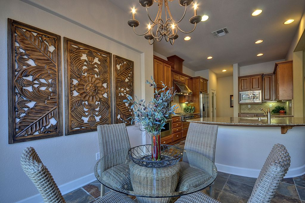Tropical Dining Room with Chandelier, Standard height, travertine floors