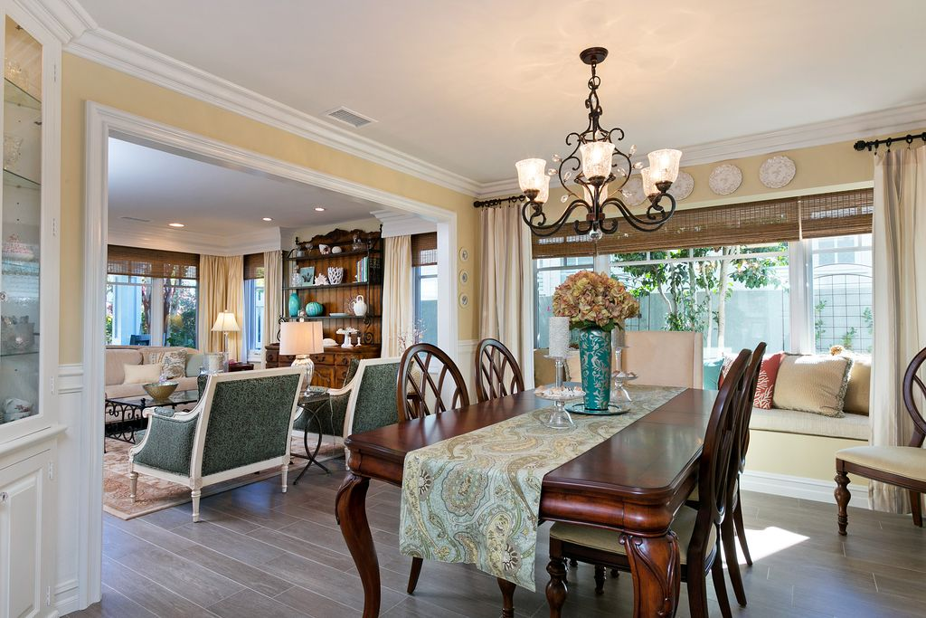 Traditional Dining Room with Window seat, Built-in bookshelf, Standard height, Chandelier, Hardwood floors, Chair rail