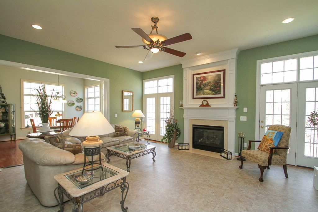 Traditional Living Room with Transom window, Minka aire santa lucia silver patina glass ceiling fan, travertine tile floors