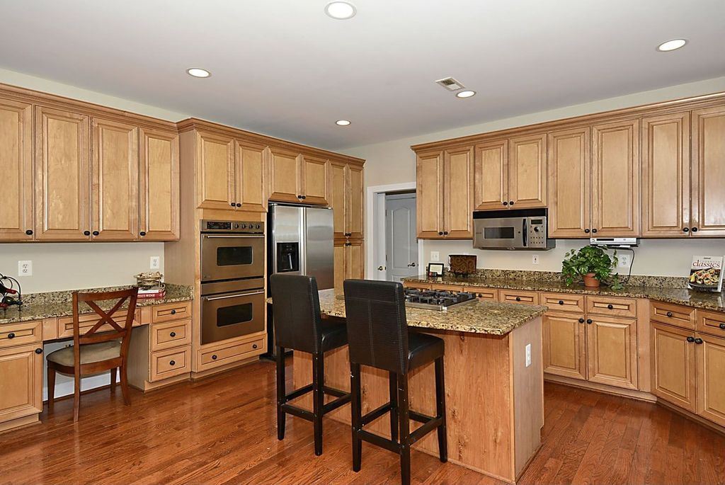 Traditional Kitchen with partial backsplash, Built In Refrigerator, Raised panel, Kitchen island, electric cooktop, Flush