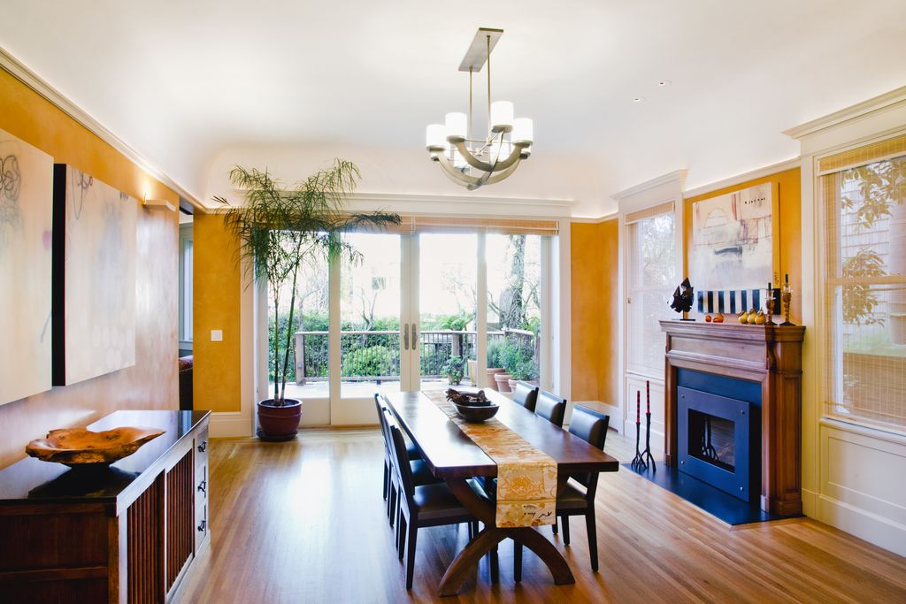 Contemporary Dining Room with metal fireplace, Chandelier, Laminate floors, Fireplace, High ceiling, Crown molding