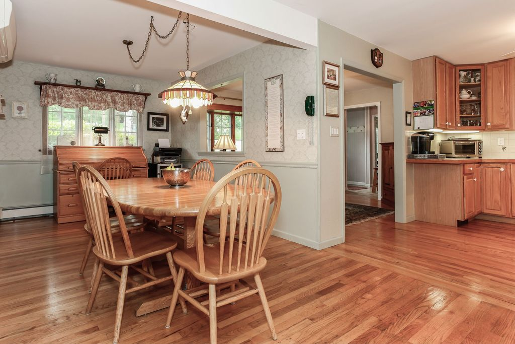 Country Dining Room with Hardwood floors, Casement, interior wallpaper, Pendant light, Standard height, Chair rail