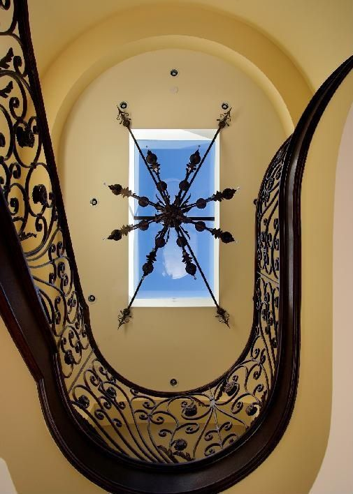Mediterranean Staircase with Cathedral ceiling, can lights, Chandelier, curved staircase, Skylight