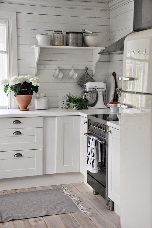 Cottage Kitchen with Wide plank floors, European Cabinets, Paint, Freestanding Full Size Top Freezer Refrigerator, Wall Hood