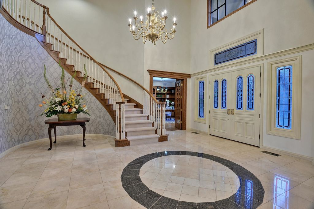 Traditional Entryway with Chandelier, interior wallpaper, picture window, stone tile floors, French doors, High ceiling