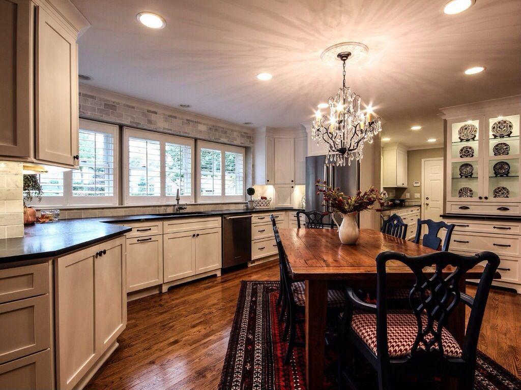 Traditional Kitchen with Stone Tile, Flat panel cabinets, Multiple Refrigerators, U-shaped, Chandelier, full backsplash
