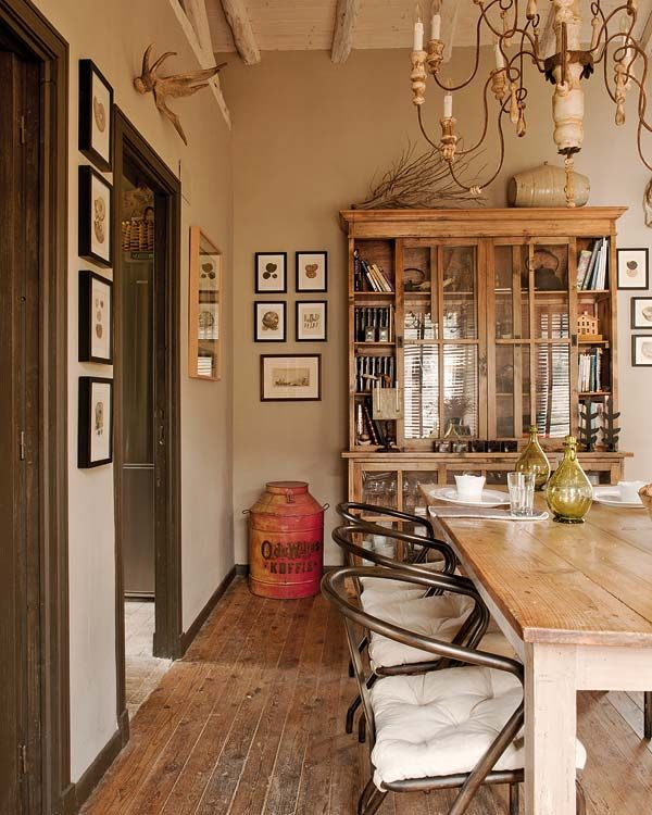 Rustic Dining Room with Built-in bookshelf, Hardwood floors, High ceiling, Exposed beam, Chandelier, Paint