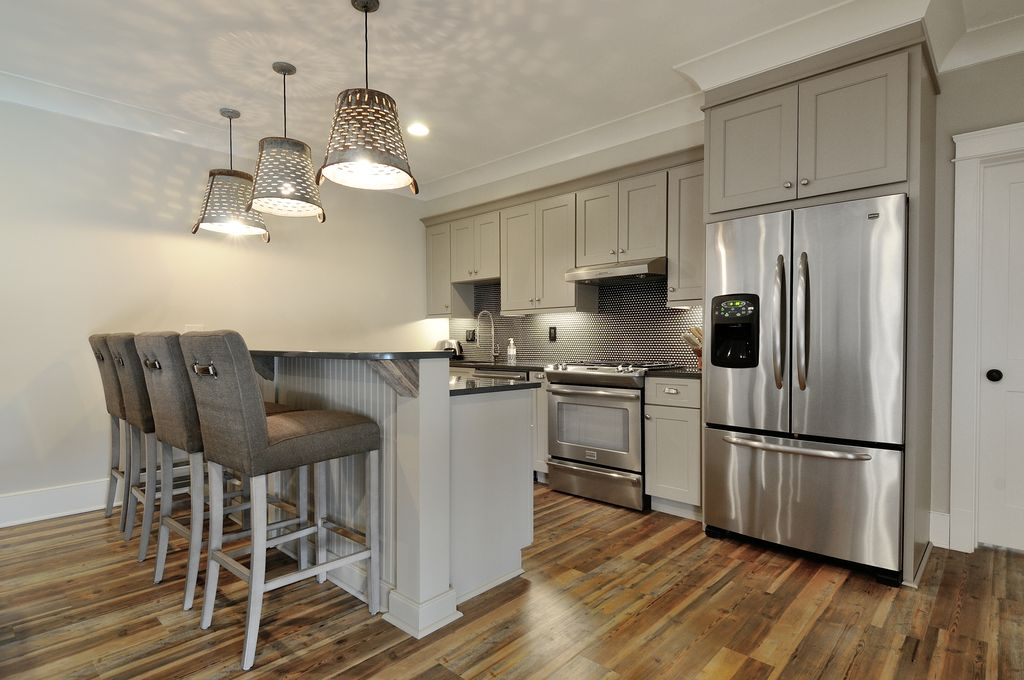 Modern Kitchen with Breakfast bar, Penny Tile, Soapstone counters, dishwasher, gas range, Wall Hood, One-wall, Pendant light