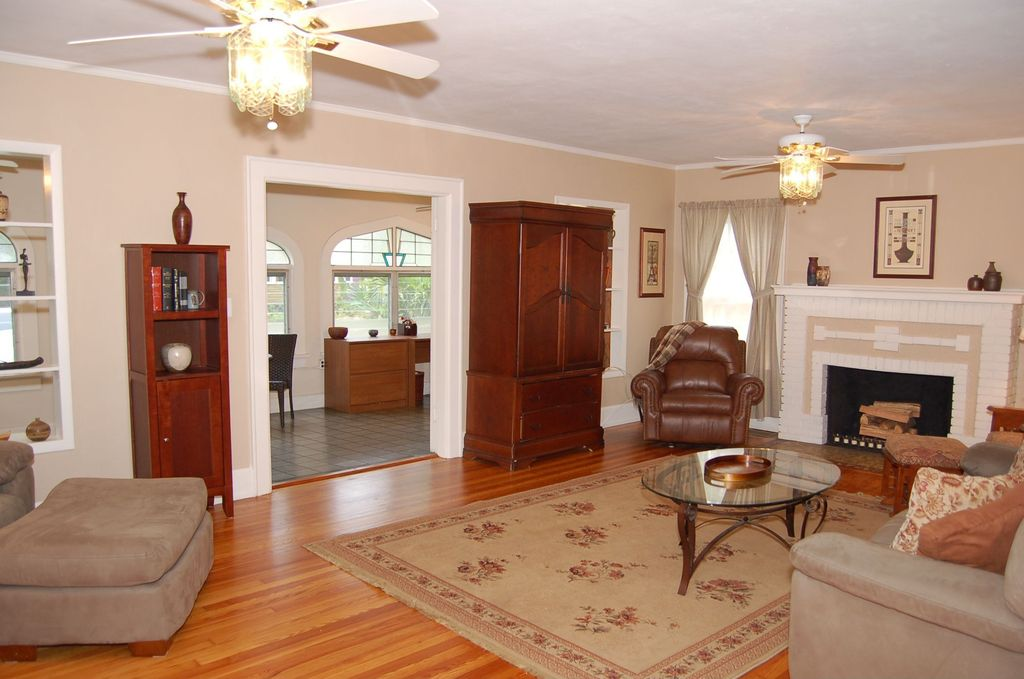 Traditional Living Room with stone fireplace, Standard height, Ceiling fan, Built-in bookshelf, Hardwood floors, Fireplace